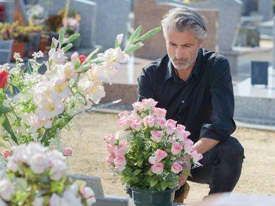 mężczyzna kładący kwiaty nagrób, cmentarz